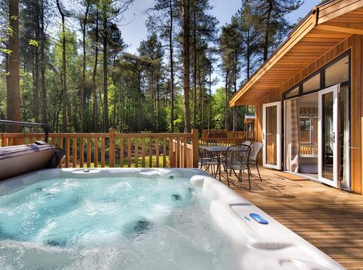 outdoor hot tub on lodge verandah surrounded by pine trees