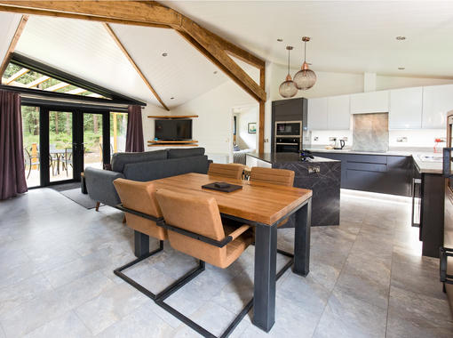 Large open plan lounge dining & kitchen area with modern dining table and feature oak beams