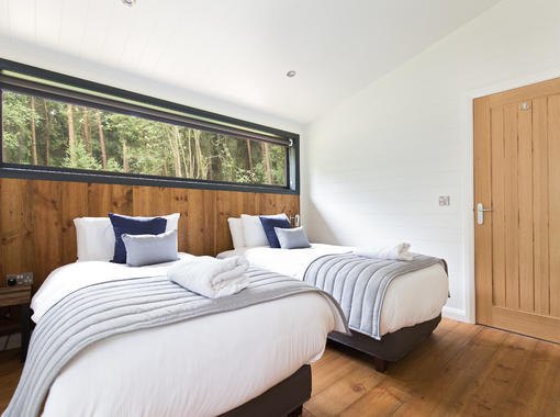 Twin bedroom with crisp white bedding with large window