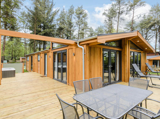 Large decking space with table and chairs for al fresco dining and relaxing sun loungers