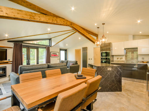 Spacious open plan lounge, dining and kitchen area with modern dining table and chairs