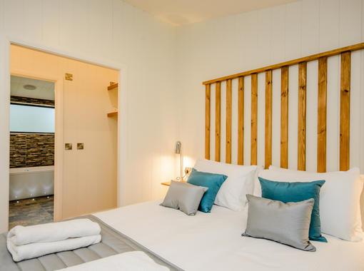 Double bedroom with feature headvoard and door leading through to en suite bathroom