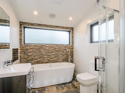 Modern bathroom with tile feature wall behind free standing bath
