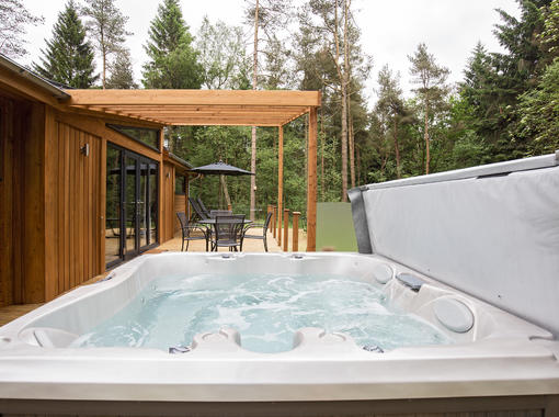 Bubbling outdoor hot tub overlooking decking area surriunded by pine trees