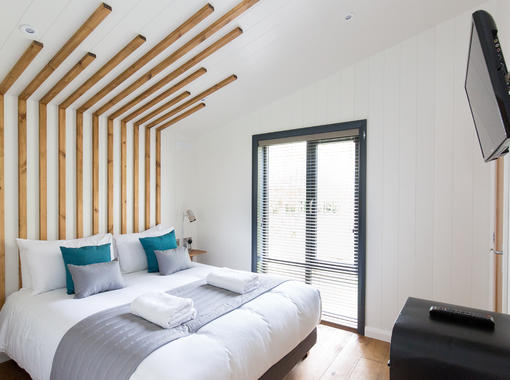 Double bedroom with feature headboard and full length windows
