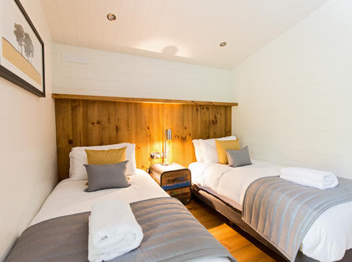 Twin bedroom with warm glow from bedside light