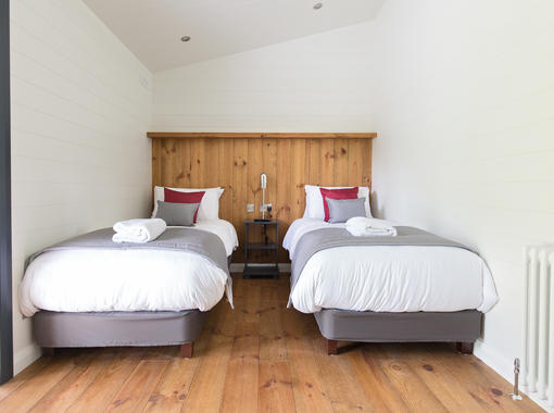 Twin bedroom with crisp white bedding and feature wooden headboard