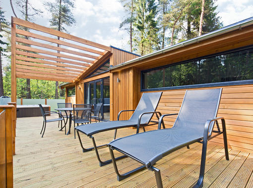 large decking area with relaxing sun loungers, table & chairs and hot tub with brise soleil