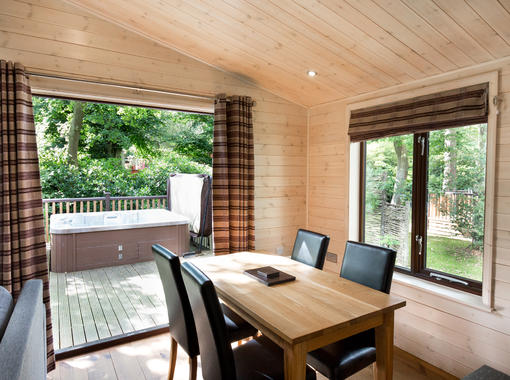 Dining area with verandah doors opening out on to decking with outdoor hot tub