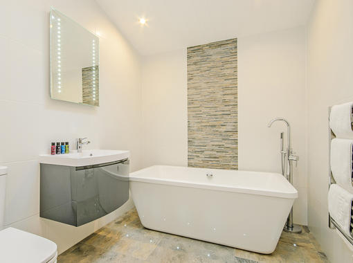Stylish bathroom with freestanding bath and tile feature wall