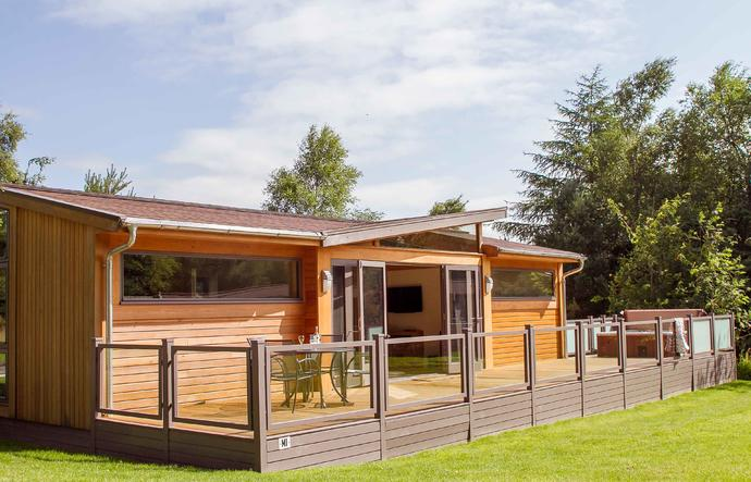 Modern lodge with large decking and hot tub