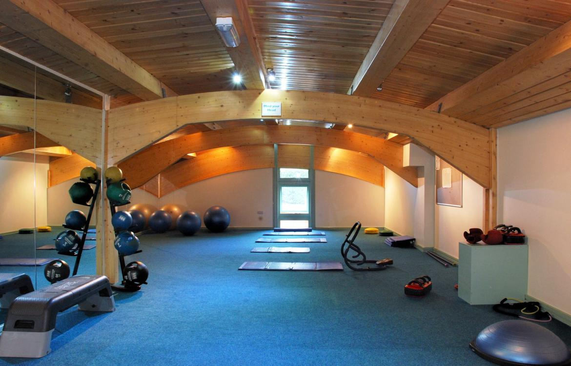 Stretch room in leisure centre with large mirrored wall, fitness balls and free wights