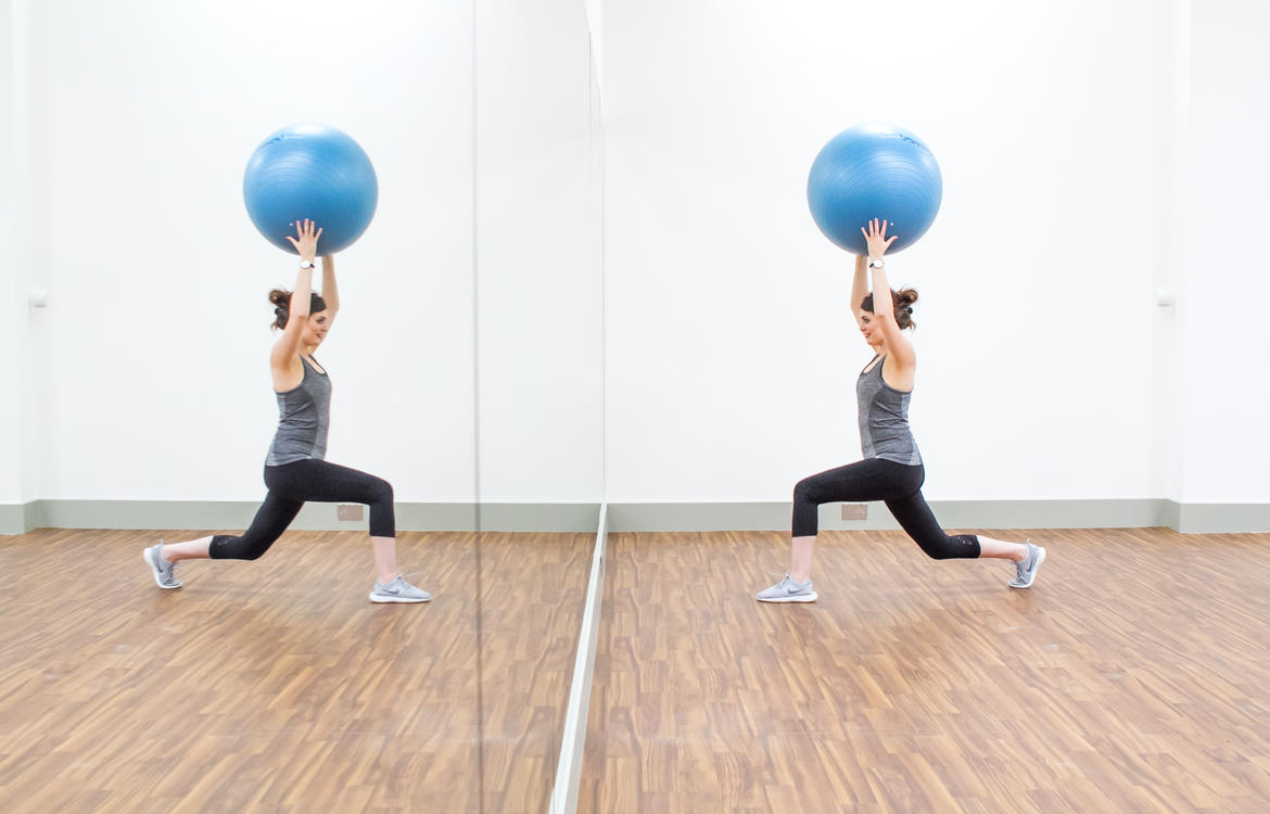 Lady in fitness studio doing exercises with gym ball in front of mirrored wall