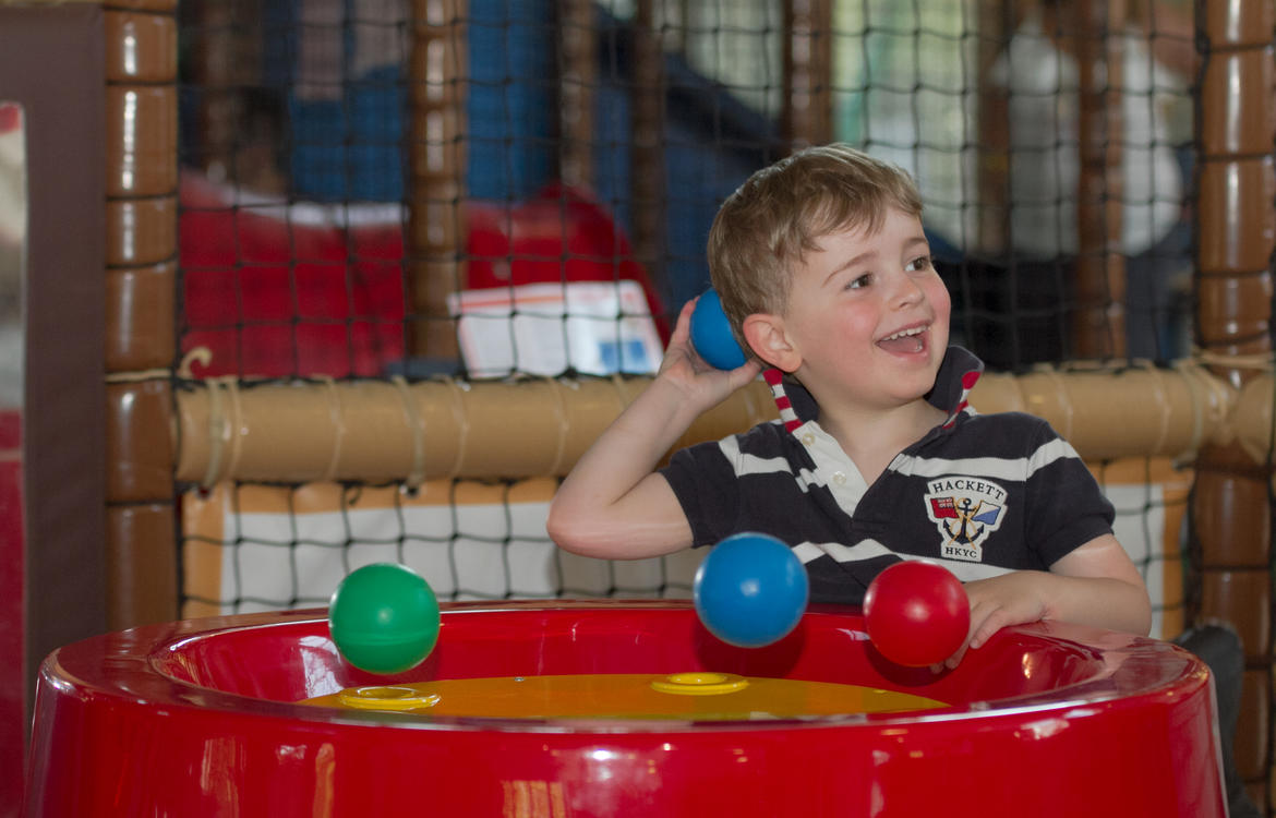 Young boy having fun with the ball machine in the toddler area