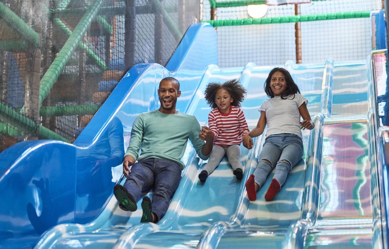 Parents & Child coming down a blue slide