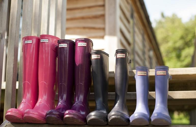 Selection of bight coloured wellies shown on the steps of a lodge