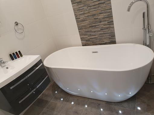 Large modern freestanding bath, surrounded by floor led lightinglighto