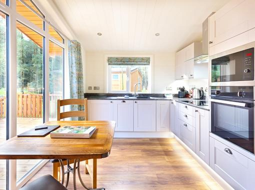 Light flooding through full height windows in to the kitchen area with dining table for 2 people