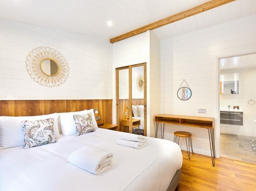 Light and airy double bedroom with crisp white bedding, door open on to en suite bathroom