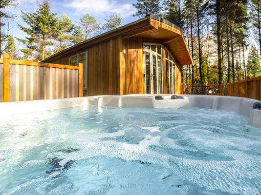 Looking out of a bubbling hot tub towards the modern lodge with pine trees in the distance