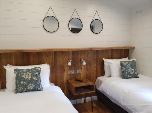 Twin bedroom with wooden headboard and 3 circular mirrors hanging behind the beds