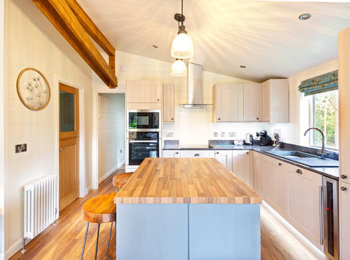 Light and stylish kitchen with central island incorporating breakfast bar
