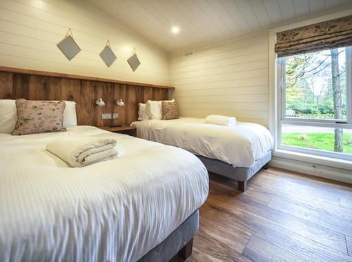 Spacious twin bedroom with light flooding in from large full height window