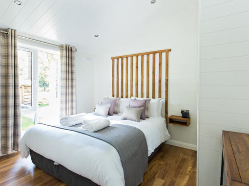 Sumptuous double bed with crisp white bedding and grey runner at the foot of bed, with full length windows
