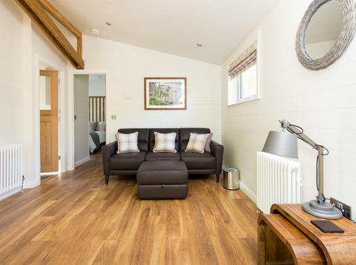 Living space with oak coloured wooden floors and comfortable brown leather sofa and footstool