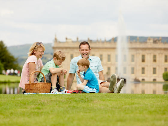 Family having a picnic next to the emperor fountain at Chatsworth with the House in the background