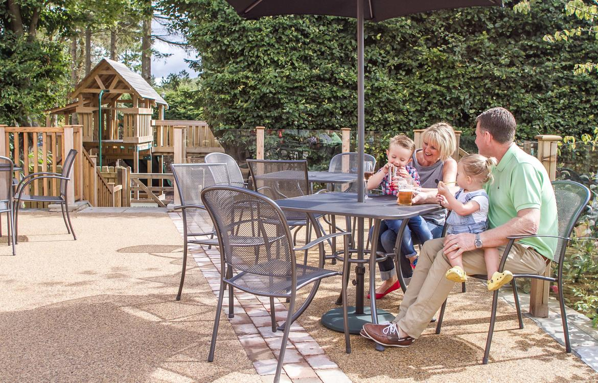 Family sat on the patio area enjoying a drink in the sunshine with the playground in the background