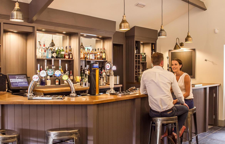 A couple sat at the bar enjoying a drink