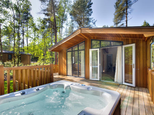 Lodge set within pine trees with beautiful blue sky, doors from lodge open onto verandah with out door hot tub