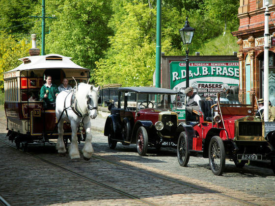 Horse drawn tram travelling past vintage cars