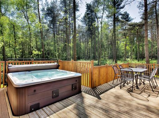 Outdoor hot tub on the verandah of a lodge within a woodland setting