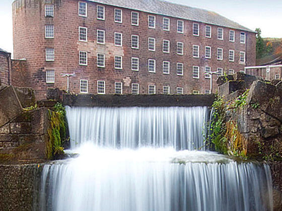 Cromford mill set in the background with waterfall in the forefront
