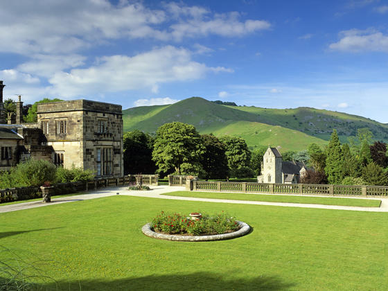 Beautiful gardens of Ilam Hall with rolling hills in the backgound