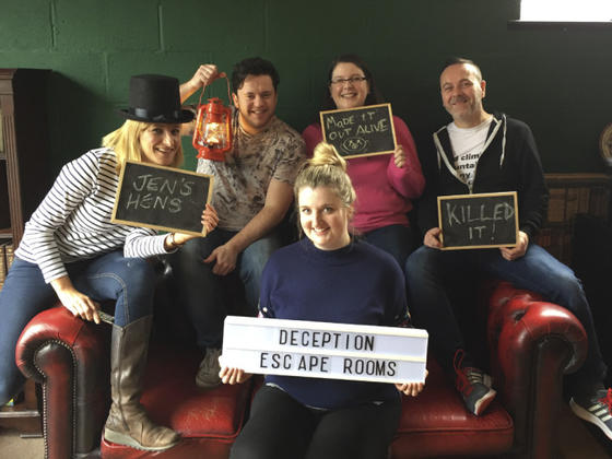 People sat on a leather sofa who have had fun in the escape rooms