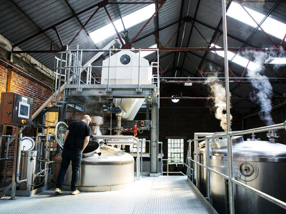 Distillery work in progress, large stainless steel vats with steam rising
