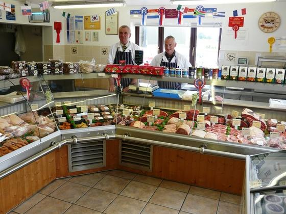 Two butchers stood behind the display counter showcasing their products