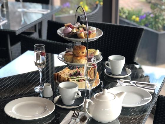 Afternoon tea on 3 tiered plates includes sandwiches, scones and sweet treats, with tea pot and glass of prosecco