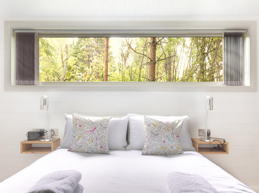 Double bed with crisp white bedding, large window above the bed head looking  out on to surrounding woodland