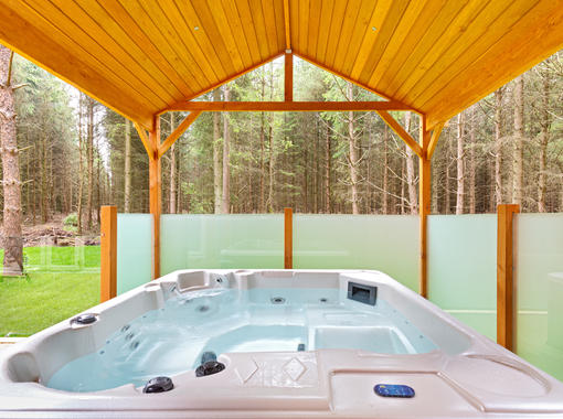 Outdoor hot tub under wooden canopy looking out on to surrounding woodland