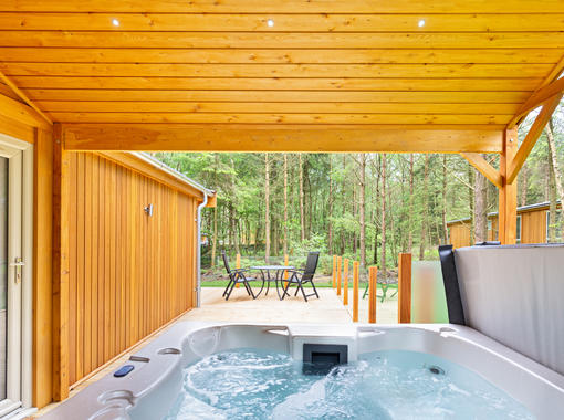 Bubbling outdoor hot tub under wooden canopy