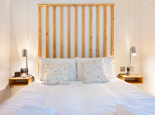 Double bed with feature wooden headboard and warm glow bedside table lamps