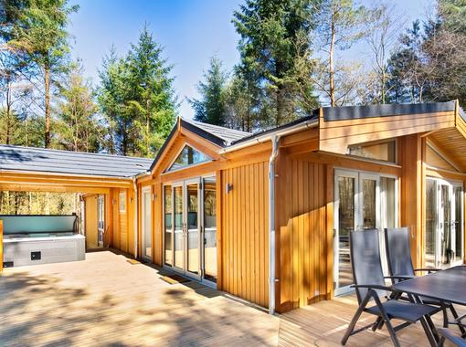 Spinney exclusive lodge with large verandah showing outdoor hot tub under wooden canopy and outdoor furniture for alfresco dining