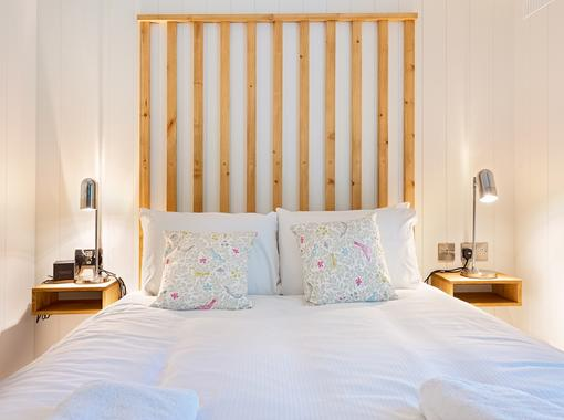 Comfortable double bed with crisp white bedding and feature wooden headboard