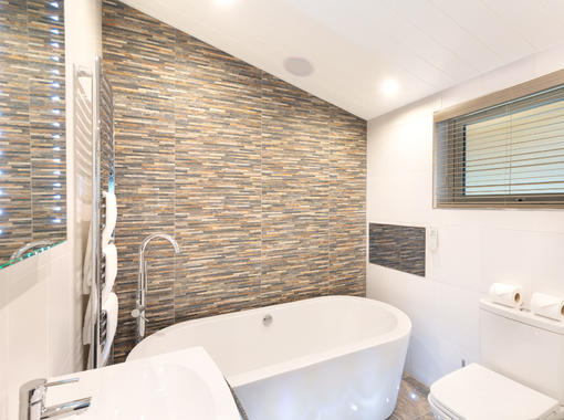 Modern bathroom with large white freestanding bath and feature tile wall