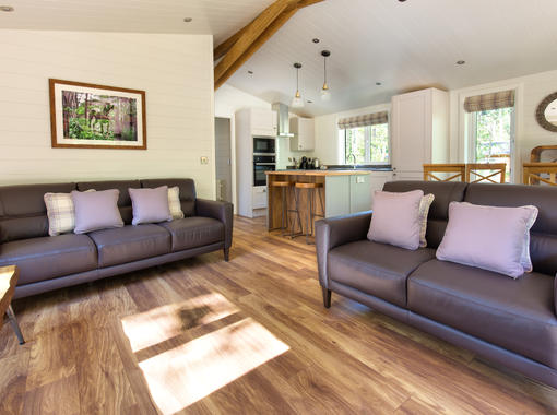 light and airy interior with sun shining onto wooden floor of open plan lounge dining and kitchen area