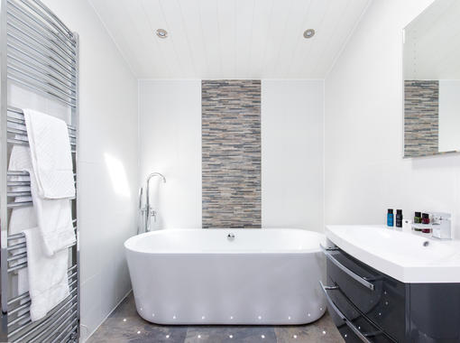freestanding bath with feature tiles, chrome towel radiator and vanity unit with mirror over